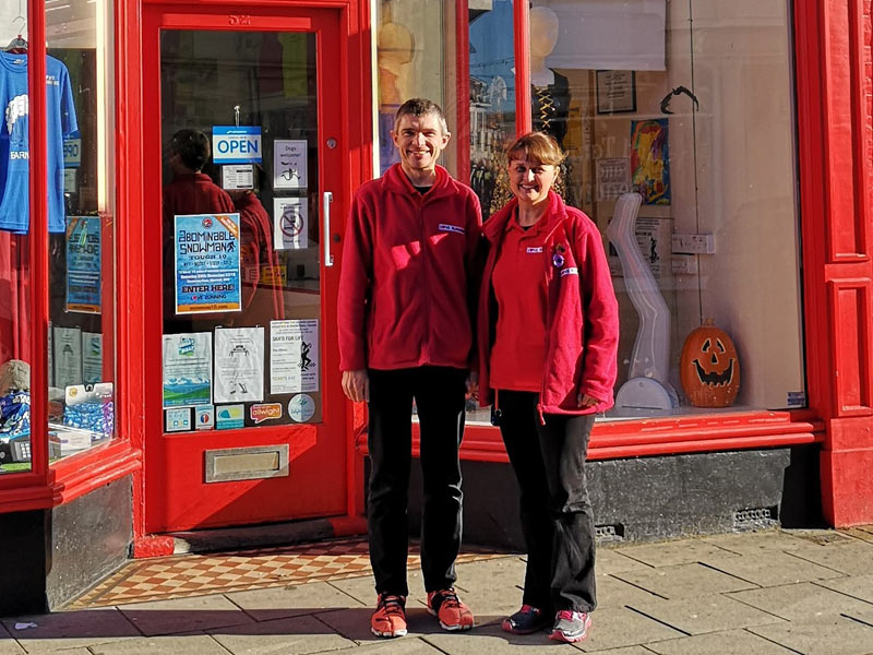 2 people standing outside their shop